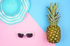 Pineapple with summer fashion accessories over a pink and blue background Royalty Free Stock Photos