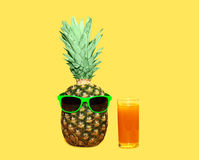 Pineapple with sunglasses and glass fruit juice on yellow background Royalty Free Stock Image