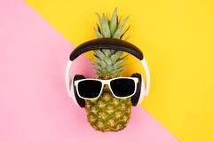 Pineapple with sunglasses and headphones over a yellow and pink background Royalty Free Stock Image