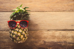 Pineapple sunglasses resting on the wooden floor concept travel. Royalty Free Stock Image