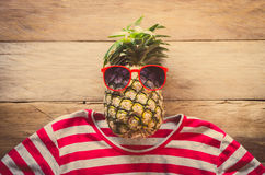 Pineapple sunglasses resting on the wooden floor concept travel. Stock Photos