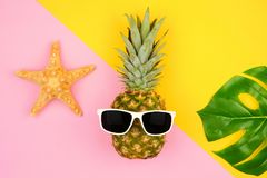 Pineapple with sunglasses and summer accessories over a pink and yellow background Royalty Free Stock Photography