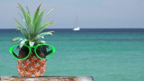 Pineapple with sunglasses, turquoise water and white boat sailing, conceptual, exotic summer holiday invitation. UHD 4K stock footage