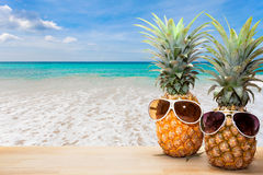 Pineapple with sunglasses on wood,concept summer background. Pineapple with sunglasses on beach background,concept summer background royalty free stock image
