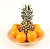 Pineapple surrounded by oranges Stock Image