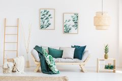 Relax room with paintings. Pineapple on table near grey settee with pillows against white wall with paintings in relax room with ladder Stock Photo