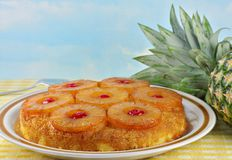 Pineapple Upside Down Cake. With a fresh whole pineapple to the side. Blue sky background has copy space stock images