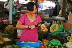 Pineapple vendor at Mekong Market. Woman cutting a pineapple at a local market in Mekong, southeast Asia Stock Photo