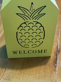 Pineapple welcome sign on wooden table royalty free stock photo