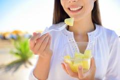 Pineapple - woman eating sliced Hawaiian fruit Stock Photography