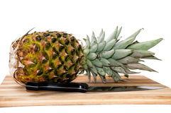Pineapple on a wooden board with knife Royalty Free Stock Image