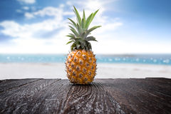 Pineapple on wooden desk and beach side background. Blue sky Stock Photos
