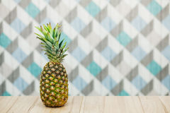 Pineapple on a wooden table over blue background. Juicy fresh ananas. Summer concept. Copy space Stock Photography
