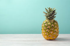 Pineapple on wooden table over mint background. Tropical summer vacation stock images