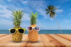 Pineapple on wooden table in a tropical landscape, Fashion hipster pineapple, Bright summer color, Tropical fruit with sunglasses royalty free stock photos