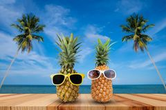 Pineapple on wooden table in a tropical landscape, Fashion hipster pineapple, Bright summer color, Tropical fruit with sunglasses stock photography