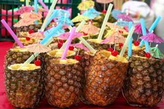 Pineapples for Pina Coladas. Pineapples carved and decorated with cherries,paper umbrellas and straws stock image