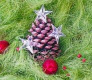 Pinecone de la Navidad adornado con las estrellas y la bola que brilla intensamente roja en fondo mullido verde Fotografía de archivo