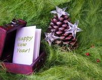 Pinecone de la Navidad adornado con las estrellas y la bola que brilla intensamente roja en fondo mullido verde Imágenes de archivo libres de regalías