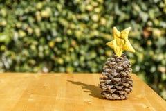 Pinecone e estrela amarela na tabela de madeira Imagens de Stock Royalty Free