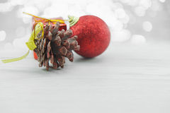 Pinecone and Red xmas ornaments on wood floor. Merry Christmas and Happy New Year. Royalty Free Stock Images