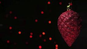 Pinecone rojo de la decoración de la Navidad sobre la guirnalda blured en fondo oscuro metrajes