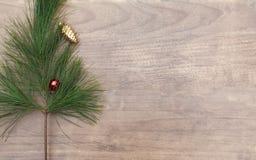 Pinecone rojo y de oro adorna la colocación en el backdro de madera blanco Fotos de archivo libres de regalías