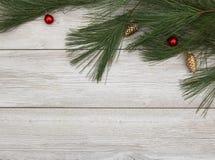 Pinecone rojo y de oro adorna la colocación en el backdro de madera blanco Imágenes de archivo libres de regalías