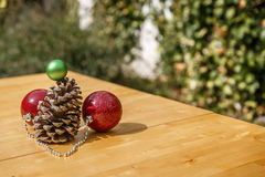 A pinecone with some Christmas balls on wooden table Stock Images