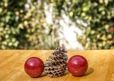 Pinecone z dwa boże narodzenie piłkami na stole Zdjęcia Stock