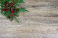 Pinecones, rode bessen, en een rood lint op een nette boeg met stock afbeelding