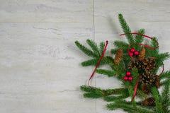 Pinecones, rode bessen, en een rood lint op een nette boeg met royalty-vrije stock foto