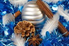 Pines cones, cinnamon sticks, star anise, feather and silvery Ch. Pines cones, cinnamon sticks, star anise, feather and silvery bauble on a blue tinsel as Royalty Free Stock Photos