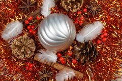 Pines cones, cinnamon sticks, star anise, feather and silvery Ch. Pines cones, cinnamon sticks, star anise, feather and silvery bauble on an orange tinsel as Royalty Free Stock Photo