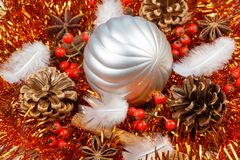 Pines cones, cinnamon sticks, star anise, feather and silvery Ch. Pines cones, cinnamon sticks, star anise, feather and silvery bauble on an orange tinsel as Royalty Free Stock Image