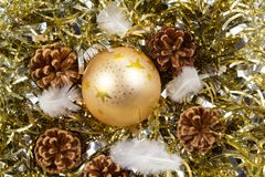 Pines cones, feather and golden Christmas ball on a golden tinse. Pines cones, feather and golden bauble on a golden tinsel as decoration for Christmas Stock Photo