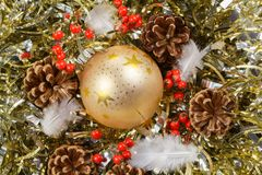 Pines cones, feather, red berries and golden Christmas ball on a. Pines cones, feather, red berries and golden bauble on a golden tinsel as decoration for Royalty Free Stock Photography