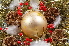Pines cones, feather, red berries and golden Christmas ball on a. Pines cones, feather, red berries and golden bauble on a golden tinsel as decoration for Royalty Free Stock Images