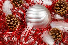 Pines cones, feather and silvery Christmas ball on a red tinsel. Pines cones, feather and silvery bauble on a red tinsel as decoration for Christmas Stock Images