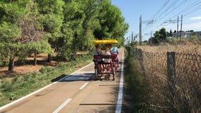 05 09 2018 Pineto, Abruzzo, Italië - familie het biking op een ricksaw in een fietssteeg tussen een pinete en een spoorweg stock footage