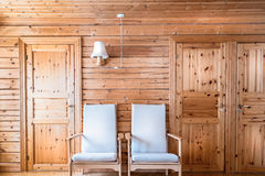 Pinewood interior wall, armchairs and doors, cabin cottage. Stock Images