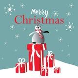Pingüino con la bufanda de la Navidad en la nieve con los regalos de la Navidad Ejemplo del vector en fondo azul con los copos de Imagenes de archivo