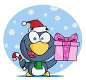 Pingüino que sostiene un bastón del regalo y de caramelo Fotografía de archivo