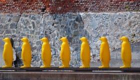 Pingüinos plásticos amarillos en fila Foto de archivo