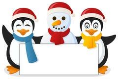 Pingüinos y muñeco de nieve con la bandera en blanco Fotos de archivo