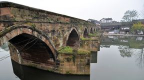 Ping Le, China: Ancient Buildings and River Bridge. A pink sandstone bridge with gothic arches spans the local river leading to a cluster of half-timber and royalty free stock image