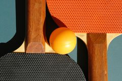 PING PONG. A closeup picture of two ping-pong rackets with an orange ball in the middle Stock Photo