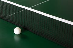 A ping-pong ball on a green table next to the net royalty free stock images