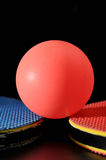 Ping pong ball with table tennis paddle. Close up of a ping pong ball with two paddles Royalty Free Stock Images