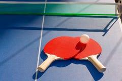 Ping-pong de los tenis de mesa dos paletas y bola blanca Imagenes de archivo